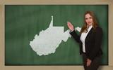Teacher showing map of west virginia on blackboard