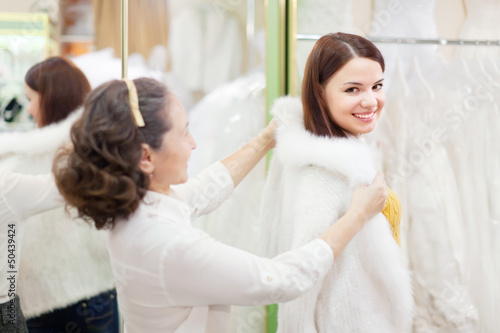 woman with girl chooses white fur cape at shop