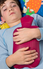 Kind / Junge mit Wärmflasche auf dem Bauch - frieren