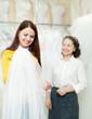 pretty bride chooses bridal veil at shop