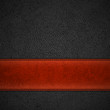 Red leather stripe on black leather background with copyspace -