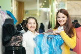 women chooses  evening gown at shop