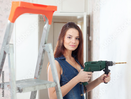 Beautiful  woman in overalls with drill