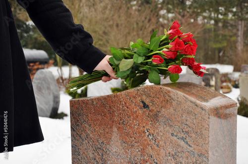Plexiglas Begraafplaats Junge Frau legt Blumen nieder