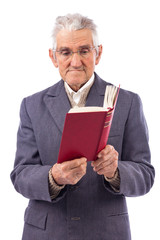 Portrait of an old man with glasses reading a book
