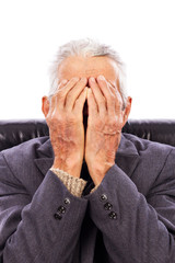Senior man covering his face with both hands