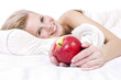Cheerful girl in lingerie on the bed, an apple in his hand.