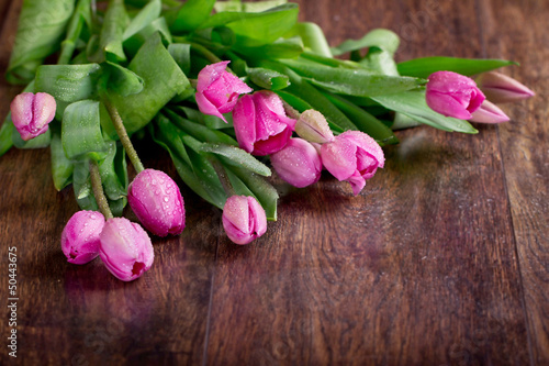 Pink tulips on a wooden background