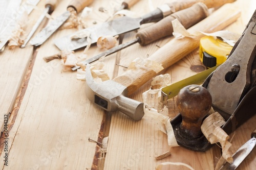 carpenter tools,hammer,meter,nails and chisel over wood table