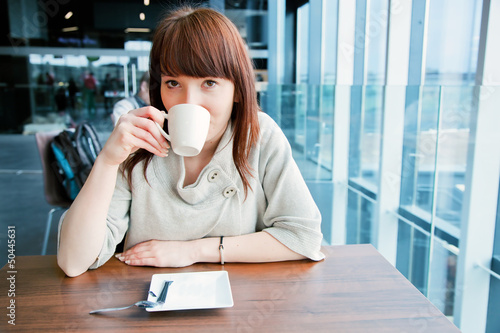 Woman drinking coffee at a corporate restaurant