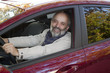 Middle-aged man with a beard driving a hot magenta car
