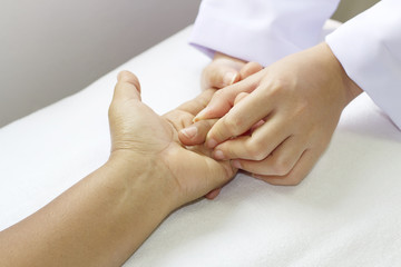Physical therapist checks range of motion patient's hand before