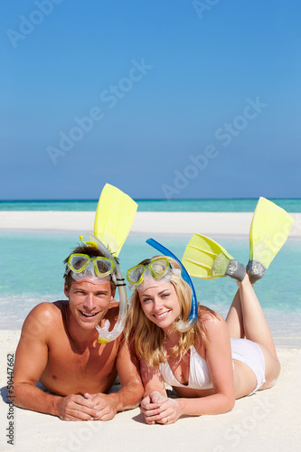 Couple With Snorkels Enjoying Beach Holiday