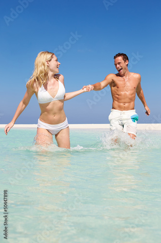 Couple Having Fun In Sea On Beach Holiday