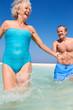 Senior Couple Having Fun In Sea On Beach Holiday
