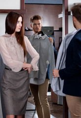 Young man asks advice of girlfriend while selecting a shirt