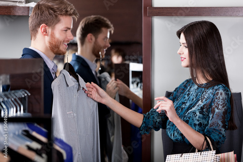 Young man consults with girlfriend while selecting shirt