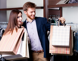 Couple with paper bags full of presents does shopping