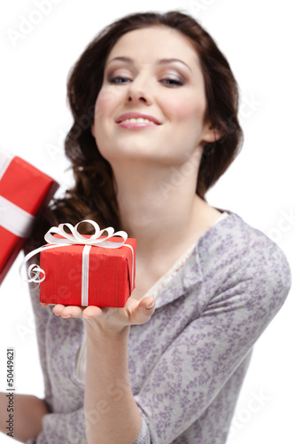 Young woman demonstrates a gift wrapped in red paper