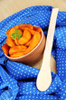 Appetizing village potatoes in bowl on blue fabric close-up