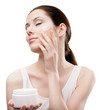 Woman putting on emollient cream from container on face