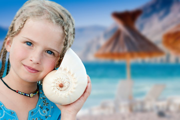 Summer joy - portrait of  lovely girl with seashell at the beach