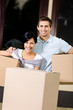 Happy couple carrying pasteboard containers