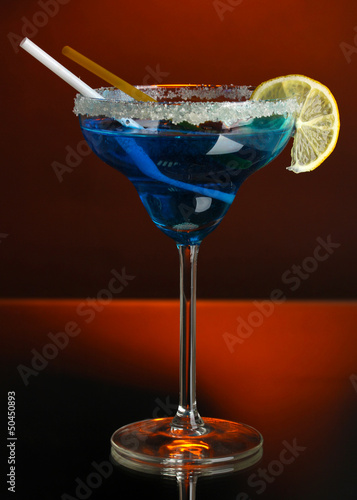 Yellow cocktail in glass on color background
