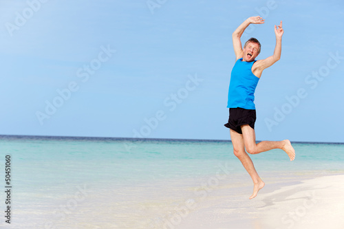 Senior Man Jumping On Beautiful Beach