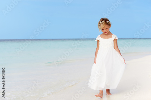 Young Girl In Bridesmaid Dress Walking On Beautiful Beach