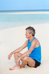 Senior Man In Sports Clothing Relaxing On Beautiful Beach