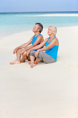 Senior Couple In Sports Clothing Relaxing On Beautiful Beach