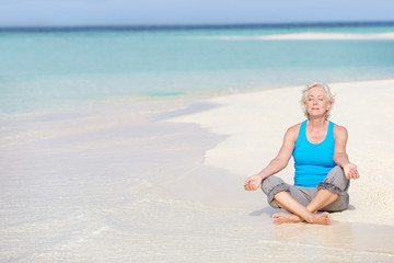 Senior Woman Meditating On Beautiful Beach