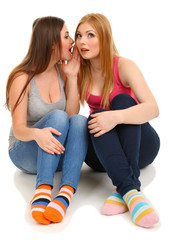 Two girl friends gossip isolated on white