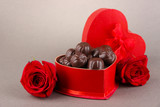 Chocolate candies in gift box, on grey background