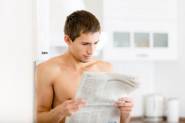 Naked man reads newspaper standing near the fridge