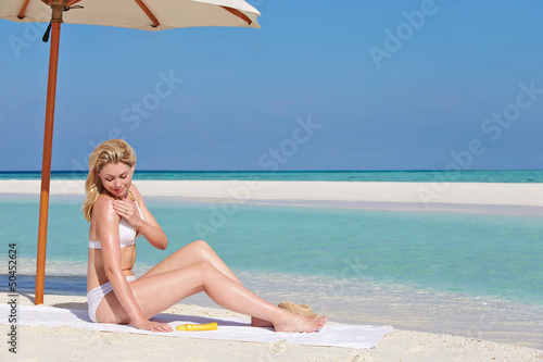 Woman Applying Sun Lotion On Beach Holiday