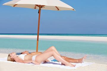 Couple Sunbathing On Beautiful Beach Holiday