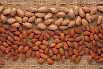 Shelled and unshelled almonds lying on sackcloth