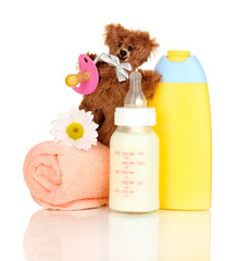 Bottle of milk, pacifier and baby cosmetic with towel isolated