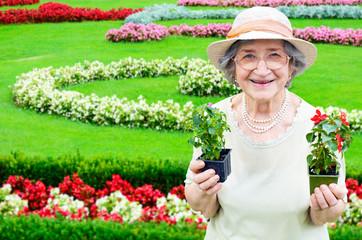 Happy senior woman holding flowers in garden