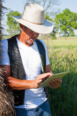 Cowboy leans on hay with tablet computer