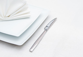 White place setting with knife and folded white napkin