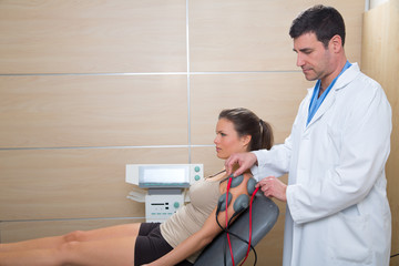 Doctor therapist checking muscle electrostimulation to woman