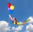 Young pretty girl fly on colorful balloons in the blue sky