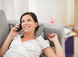 Happy young woman laying on couch and talking mobile phone