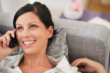 Happy young woman laying on sofa and talking mobile phone