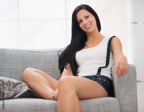 Happy girl sitting on couch in living room