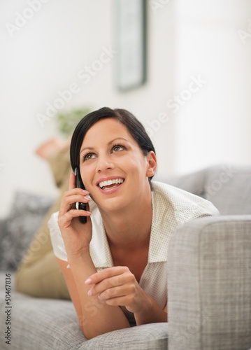 Happy young woman laying on couch and talking cell phone