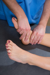 Ankle joint mobilization therapy of doctor man to woman